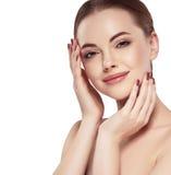 Kvinna med den härliga framsidan, sund hud och hennes hår på ett tillbaka trycka på hennes framsida med fingrar tätt upp ståendes Fotografering för Bildbyråer