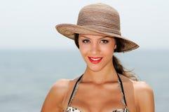 Kvinna med den härliga hatten på en tropisk strand Fotografering för Bildbyråer