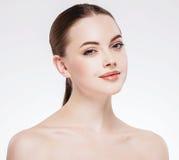 Kvinna med den härliga framsidan, sund hud och hennes hår på ett tillbaka slut upp ståendestudio på vit Royaltyfri Fotografi