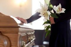 Kvinna med den liljablommor och kistan på begravningen royaltyfri foto