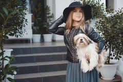Kvinna med den lilla hunden i stadsgata Arkivfoto