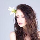 Kvinna med den långa lockigt hår och liljan i hår som ner ser Spa och skönhet Royaltyfri Fotografi
