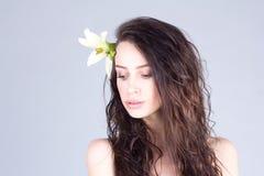 Kvinna med den långa lockigt hår och liljan i hår som ner ser Spa och skönhet Royaltyfri Foto