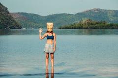 Kvinna med den pappers- påsen som är över huvudet på den tropiska stranden Royaltyfria Foton