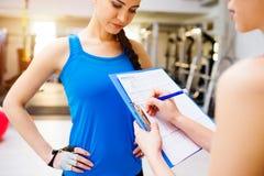 Kvinna med den personliga instruktören i idrottshallen, plan på skrivplattan Arkivfoto