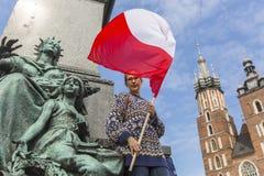 Kvinna med den polska flaggan i den huvudsakliga fyrkanten av Krakow Royaltyfri Bild