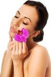 Kvinna med den purpurfärgade orkidén och stängda ögon Royaltyfri Fotografi
