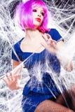 Kvinna med den purpurfärgade wigen och intensiva sminket som fångas i en spindelrengöringsduk Arkivfoton