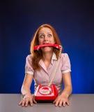 Kvinna med den röda telefonen i hennes mun Arkivbild