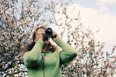 Kvinna med den retro kameran för tappning som går i parkera Royaltyfri Foto