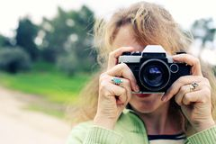 Kvinna med den retro kameran för tappning som går i parkera Arkivbild