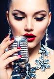 Kvinna med den Retro mikrofonen Arkivbild