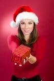 Kvinna med den santa hatten som ger en julgåvaask arkivbild