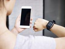 Kvinna med den smarta telefonen och klockan arkivfoton