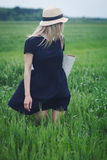 Kvinna med den svarta klänningen i ett fält av grönt vete Royaltyfri Fotografi