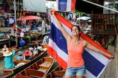 Kvinna med den Thailand flaggan på Bangkok som svävar marknaden royaltyfria foton