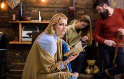 Kvinna med den trötta blickläseboken Den blonda kvinnan i blå skjorta och jeans slogg in den woolen filten som tycker om afton me Royaltyfria Foton