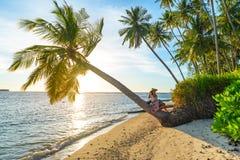 Kvinna med den traditionella asiatiska hatten som kopplar av p? den tropiska stranden som sitter p? kokosn?tpalmtr?det i sunburst arkivbild