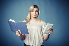 Kvinna med den traditionella bok- och eBookavläsarminnestavlan royaltyfri bild