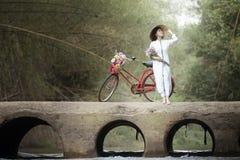 Kvinna med den traditionella klänningen för Vietnam kultur, Ao dai och cykeln royaltyfri fotografi