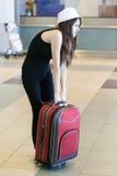 Kvinna med den tunga resväskan i flygplatsen royaltyfria bilder