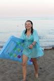 Kvinna med den uppblåsbara madrassen på strand royaltyfri foto