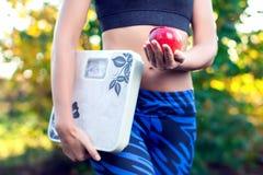 Kvinna med den utomhus- skalan och röda äpplet Att banta bantar och healt royaltyfri fotografi