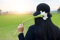 Kvinna med den vita blomman, i att koppla av för hand som är utomhus- i lantlig landskapsolnedgång royaltyfria foton