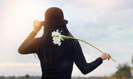 Kvinna med den vita blomman, i att koppla av för hand som är utomhus- i lantligt landskap royaltyfri bild