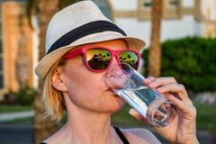 Kvinna med den vita hatten och rosa solglasögon med trevlig reflexion av palmträd och solnedgången som dricker nytt rent vatten royaltyfri fotografi