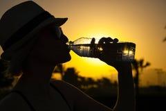 Kvinna med den vita hatten och rosa solglasögon med trevlig reflexion av palmträd och solnedgången som dricker nytt rent vatten royaltyfri foto