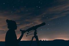 Kvinna med det astronomiska teleskopet Natthimmel, med moln och Co Royaltyfri Foto