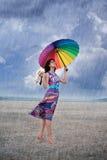 Kvinna med det färgrika paraplyet under regnet Arkivbild