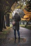 Kvinna med det genomskinliga paraplyet på en regnig dag Fotografering för Bildbyråer