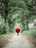 Kvinna med det röda paraplyet som poserar i höstlandskapet royaltyfri fotografi
