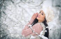 Kvinna med det vita pälslocket som ler tycka om vinterlandskapet i skogsidosikt av den lyckliga brunettflickan som spelar med snö Arkivbild