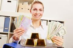 Kvinna med dollar och euro och guld royaltyfria foton