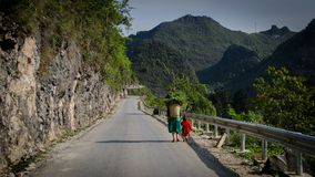 Kvinna med dottern i traditionell vietnamesisk kläder med en korg bak hennes baksida som går på vägen fotografering för bildbyråer