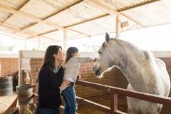 Kvinna med dottern som trycker på hästen i ladugård arkivfoton