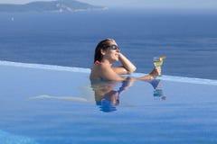 Kvinna med drinken i oändlighetspöl Royaltyfria Bilder