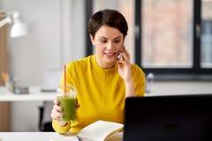 Kvinna med drinken som kallar p? smartphonen p? kontoret royaltyfria foton