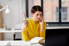 Kvinna med drinken som kallar p? smartphonen p? kontoret royaltyfria bilder