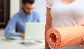 Kvinna med en övning som är matt i en kontorsbakgrund arkivfoto