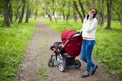 kvinna med en barnvagn Fotografering för Bildbyråer