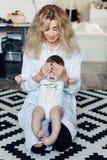 Kvinna med en behandla som ett barn i hennes armar i rummet Royaltyfria Foton
