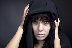 Kvinna med en blek framsida i black Arkivfoto