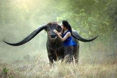 Kvinna med en buffel Royaltyfria Bilder