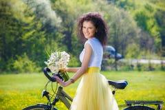 kvinna med en cykel i natur Arkivfoton