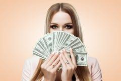 Kvinna med en fan av pengar i henne händer Skönhetståenden av unga flickan täcker hennes framsida med pengar Räkningar av 100 USD Arkivfoto
