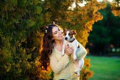 Kvinna med en favorit- hundavel Jack Russell Terrier som spelar i den härliga trädgården royaltyfri fotografi